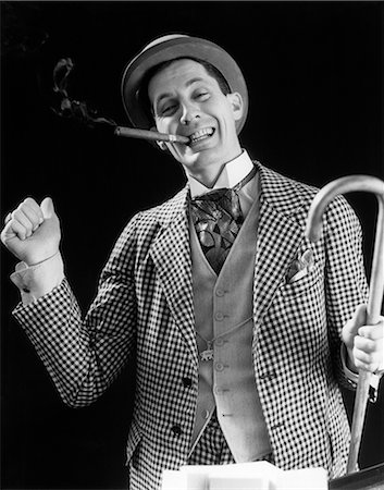 1930s SMILING MAN CARNIVAL BARKER CON MAN IN CHECKERED SUIT WITH CANE IN HAND & CIGAR IN MOUTH LOOKING AT CAMERA Stock Photo - Rights-Managed, Code: 846-08512750
