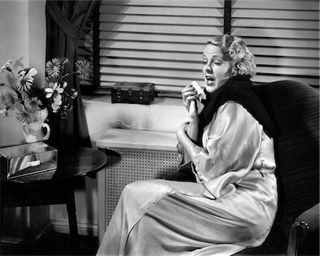 1930s WOMAN SNEEZING COUGHING WITH COLD SITTING NEXT TO RADIATOR FOR HEAT WARMTH Stock Photo - Rights-Managed, Code: 846-08639469