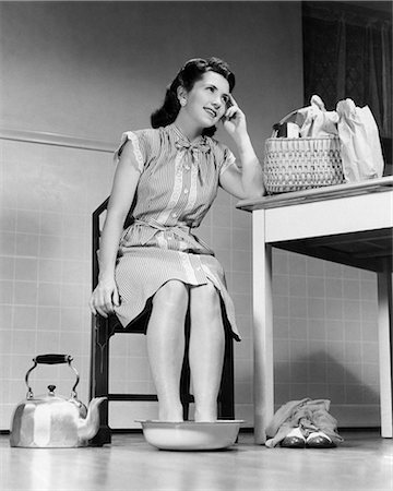1940s HOUSE WIFE WOMAN HOME FROM GROCERY SHOPPING SHOES OFF SORE FEET SOAKING PAN OF HOT WATER Stock Photo - Rights-Managed, Code: 846-08639472