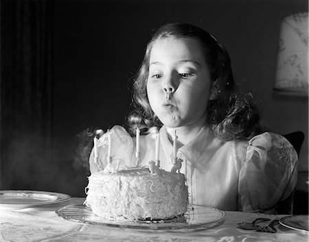1950s GIRL IN PARTY DRESS BLOWING OUT CANDLES ON BIRTHDAY CAKE WITH 5 CANDLES Stock Photo - Rights-Managed, Code: 846-08639539