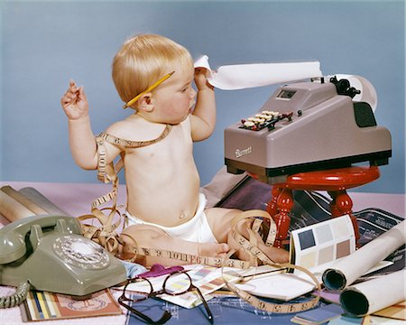 1960s DESIGNER BABY SITTING TANGLED IN MEASURING TAPE WITH ADDING MACHINE BLUE PRINTS TELEPHONE PAINT SAMPLES Stock Photo - Rights-Managed, Code: 846-08639544