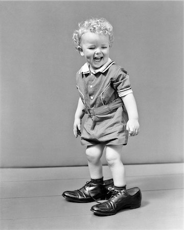 1930s 1940s LAUGHUNG CURLY BLOND HEADED BABY BOY WALKING IN FATHER'S ADULT SHOES FOLLOWING FOOTSTEPS Stock Photo - Rights-Managed, Code: 846-08639540