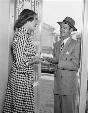 1950s HOUSEWIFE IN GINGHAM DRESS AT DOOR OF HOME TALKING TO SALESMAN IN SUIT & HAT HOLDING PENCIL & PAD Stock Photo - Rights-Managed, Code: 846-08639575