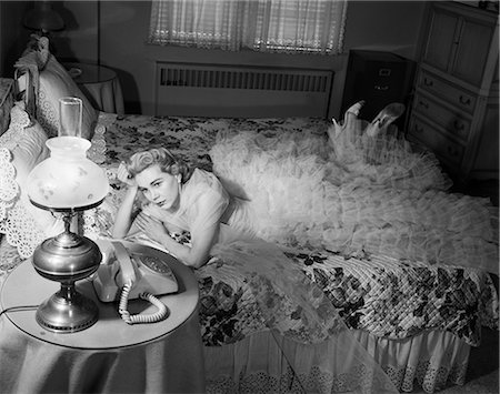 1950s SAD BLOND WOMAN LOOKING STOOD UP WEARING CHIFFON RUFFLED EVENING GOWN LYING ON BED WAITING BY TELEPHONE Stock Photo - Rights-Managed, Code: 846-08639579