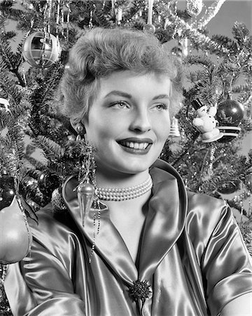 1940s 1950s PORTRAIT SMILING WOMAN WITH CHRISTMAS TREE WEARING SATIN BLOUSE PEARL NECKLACE Stock Photo - Rights-Managed, Code: 846-08639588