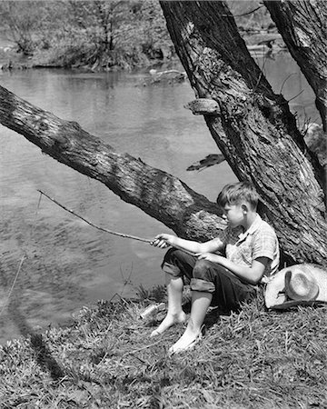 1940s BAREFOOT BOY SITTING UNDER TREE BY STREAM FISHING WITH TWIG POLE Stock Photo - Rights-Managed, Code: 846-08721074