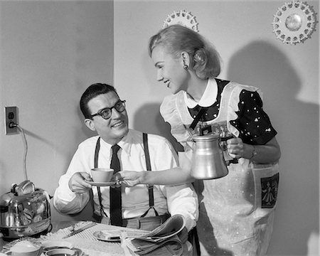 1950s COUPLE AT BREAKFAST TABLE MAN READING NEWSPAPER SMILING AT WIFE HOLDING COFFEE CUP AND PERCOLATOR POT Stock Photo - Rights-Managed, Code: 846-08721086