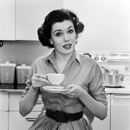 1950s 1960s PORTRAIT WOMAN HOUSEWIFE IN KITCHEN DRINKING CUP OF COFFEE SPEAKING LOOKING AT CAMERA Stock Photo - Rights-Managed, Code: 846-08721088