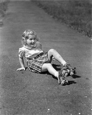 1940s GIRL FALLING DOWN SITTING ON  SIDEWALK WEARING METAL ROLLER SKATES Stock Photo - Rights-Managed, Code: 846-08721095