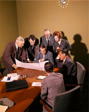 1950s 1960s SEVEN BUSINESS PEOPLE GATHERED AROUND IN A MEETING EXAMINING A PROJECT Stock Photo - Rights-Managed, Code: 846-08721109