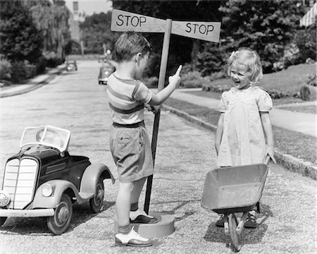 female police officer happy - 1930s 1940s BOY PLAYING TRAFFIC COP POINTING TO STOP SIGN HALTING GIRL WITH WHEELBARROW Stock Photo - Rights-Managed, Code: 846-08721101