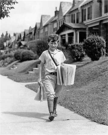 1930s BOY NEWSBOY LOOKING AT CAMERA DELIVERING NEWSPAPERS WALKING ALONG SUBURBAN STREET OF ROW HOUSES Stock Photo - Rights-Managed, Code: 846-08721102
