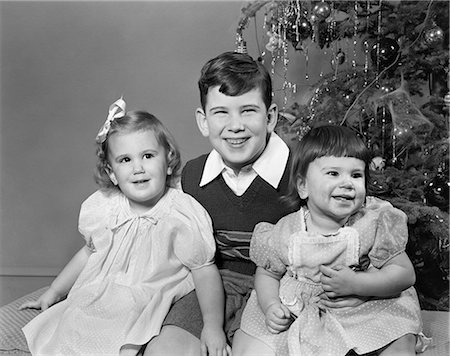 1940s 1950s SMILING BIG BROTHER AND TWO SISTERS SITTING TOGETHER BY CHRISTMAS TREE Stock Photo - Rights-Managed, Code: 846-08721139