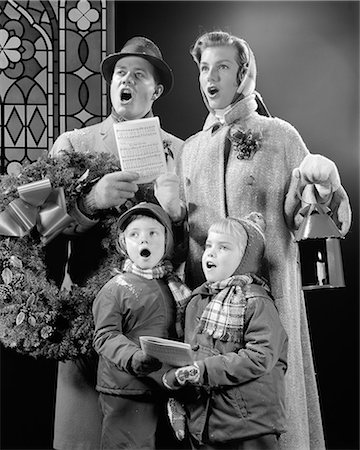 1950s FAMILY OF FOUR SON DAUGHTER SINGING CHRISTMAS CAROLS DAD HOLDING WREATH MOM HOLDING CANDLE LANTERN Stock Photo - Rights-Managed, Code: 846-08721140