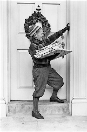 1930s 1940s BOY HOLDING WRAPPED PACKAGES RINGING BELL ON DOOR WITH CHRISTMAS WREATH Stock Photo - Rights-Managed, Code: 846-08721141