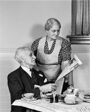 1940s ELDERLY COUPLE MAN WOMAN IN KITCHEN MAN SITTING AT TABLE WOMAN LOOKING OVER HIS SHOULDER READING NEWSPAPER Stock Photo - Rights-Managed, Code: 846-09013096
