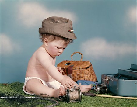 1960s BABY READY TO GO FISHING WEARING HAT SURROUNDED BY TACKLE BOX FISHING ROD NET BASKET Stock Photo - Rights-Managed, Code: 846-02794001