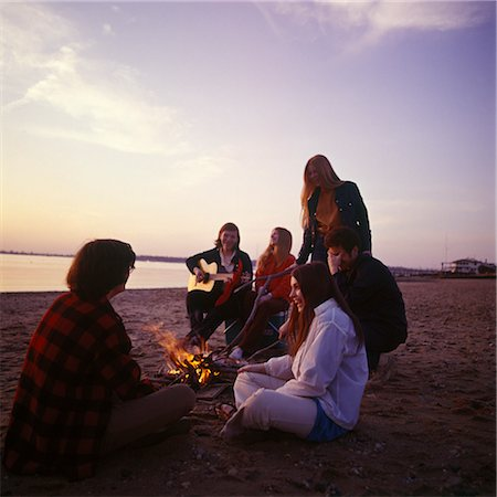 1970s GROUP TEENAGER BOYS GIRLS TOGETHER SEASHORE SHORE CAMPFIRE GUITAR SINGING RETRO SAND SUNSET OCEAN BEACH OUTDOOR Stock Photo - Rights-Managed, Code: 846-02794129