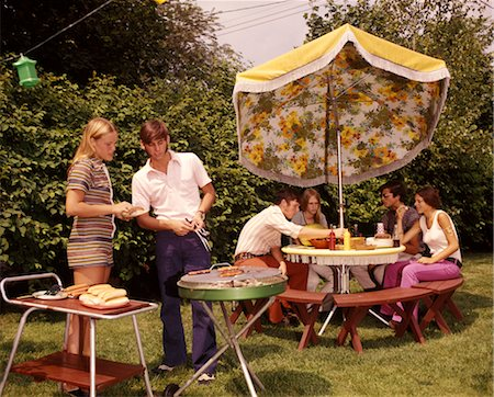 1960 1960s 1970 1970s GROUP TEENS TEEN AGED TEENAGERS BOYS GIRLS BACKYARD BBQ GRILL GRILLING TABLE UMBRELLA SUMMER Stock Photo - Rights-Managed, Code: 846-02794134