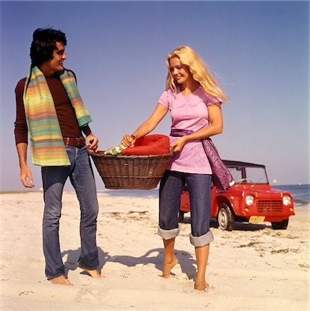 1970s COUPLE BEACH CARRY PICNIC BASKET RED DUNE BUGGY IN BACKGROUND Stock Photo - Rights-Managed, Code: 846-02794131