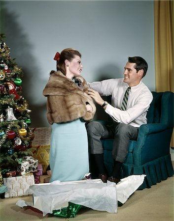 1970s LIFESTYLE COUPLE MAN ADJUSTING NEW HOLIDAY GIFT FUR JACKET ON WIFE IN LIVING ROOM BESIDE CHRISTMAS TREE Stock Photo - Rights-Managed, Code: 846-02794230