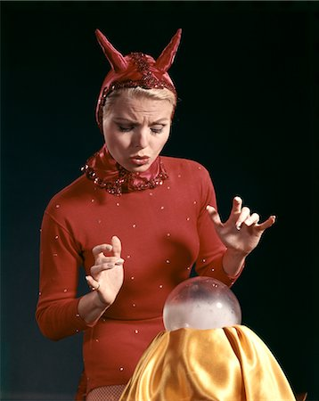 1960s BLOND WOMAN IN RED DEVIL COSTUME WITH HORNS LOOKING SURPRISED AT A CRYSTAL BALL Stock Photo - Rights-Managed, Code: 846-02794278