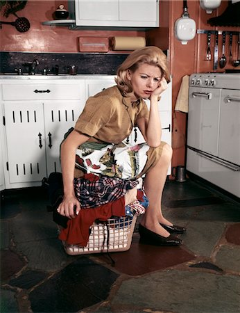 1960s TIRED HOUSEWIFE SITTING ON TOP OF LAUNDRY BASKET IN KITCHEN Stock Photo - Rights-Managed, Code: 846-02794354