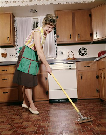 1960s WOMAN IN APRON CLEANING KITCHEN FLOOR WITH SPONGE MOP Stock Photo - Rights-Managed, Code: 846-02794358