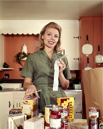 1960s YOUNG BLOND HOUSEWIFE SMILING WHILE CHECKING GROCERY SHOPPING RECEIPT IN KITCHEN Stock Photo - Rights-Managed, Code: 846-02794350