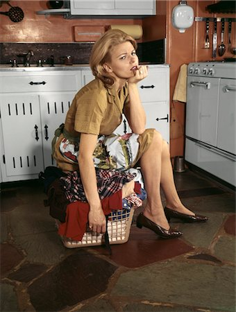 1960s TIRED HOUSEWIFE SITTING ON TOP OF LAUNDRY BASKET IN KITCHEN Stock Photo - Rights-Managed, Code: 846-02794353