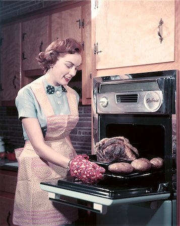 simsearch:846-02793283,k - 1950s SMILING WOMAN HOUSEWIFE WEARING APRON AND OVEN MITTS TAKING ROAST BEEF WITH POTATOES OUT OF KITCHEN OVEN Stock Photo - Rights-Managed, Code: 846-02794393
