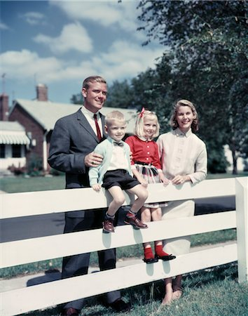 1950s 1960s FAMILY PORTRAIT MOTHER FATHER DAUGHTER SON AT WHITE FENCE OF SUBURBAN HOME Stock Photo - Rights-Managed, Code: 846-02794425
