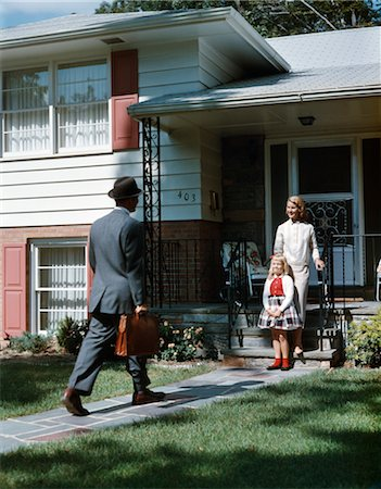 1950s WOMAN MOTHER GIRL DAUGHTER WAITING AT FRONT STEPS SUBURBAN HOUSE FOR MAN FATHER WITH BRIEFCASE COMING HOME Stock Photo - Rights-Managed, Code: 846-02794426