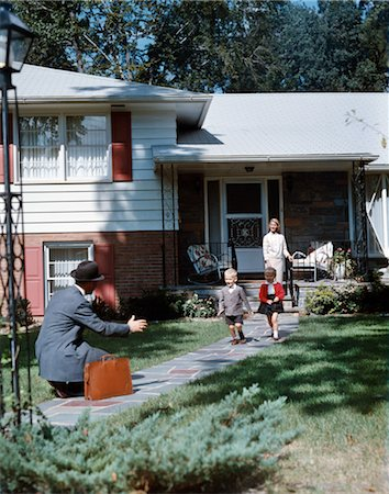 1950s FATHER COMING HOME KNEELING ARMS EXTENDED BOY GIRL RUNNING TO WELCOME HIM WOMAN STAND SUBURBAN HOUSE FAMILY Stock Photo - Rights-Managed, Code: 846-02794428