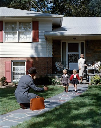 1950s FAMILY WOMAN MOTHER WATCHING MAN FATHER COMING HOME TO SUBURBAN HOUSE KNEELING ARMS EXTENDED TO BOY SON GIRL DAUGHTER RUNNING TO WELCOME HIM HOME Stock Photo - Rights-Managed, Code: 846-02794429
