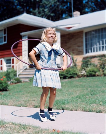 1950s 1960s YOUNG BLOND GIRL PLAYING WITH HULA HOOP OUTSIDE ON SUBURBAN SIDEWALK IN SAILOR STYLE DRESS Stock Photo - Rights-Managed, Code: 846-02794423