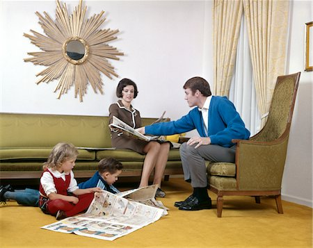 1970s MOTHER AND FATHER READING SUNDAY PAPER WITH SON AND DAUGHTER IN LIVING ROOM SUNBURST MIRROR MAN WOMAN BOY GIRL Stock Photo - Rights-Managed, Code: 846-02794477