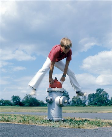 RETRO 1970s BOY JUMPING OVER FIRE HYDRANT Stock Photo - Rights-Managed, Code: 846-02794520