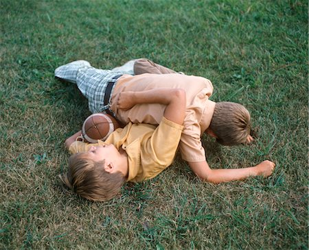 TWO BOYS WRESTLING PLAYING FOOTBALL TACKLE ON LAWN Stock Photo - Rights-Managed, Code: 846-02794521