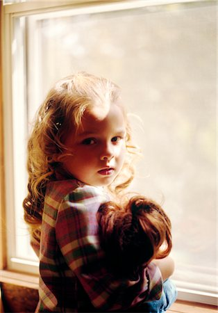 1970s SAD BLOND GIRL HOLDING DOLL STANDING BY WINDOW Stock Photo - Rights-Managed, Code: 846-02794579