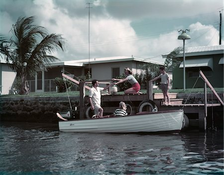 1950s FAMILY LOADING PICNIC INTO SMALL WOODEN MOTOR BOAT DINGHY MOM DAD BOY GIRL MAN WOMAN TROPICAL DOCK PALM HOUSE Stock Photo - Rights-Managed, Code: 846-02794606