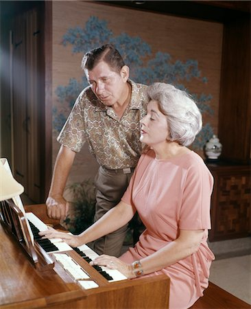 1950s 1960s MATURE COUPLE MAN AND WOMAN PLAYING AND SINGING TOGETHER AT HOME ORGAN KEYBOARD INSTRUMENT Stock Photo - Rights-Managed, Code: 846-02794727