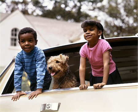 1970s SMILING AFRICAN AMERICAN BOY AND GIRL AND AIREDALE DOG LEANING OUT OF STATION WAGON REAR WINDOW Stock Photo - Rights-Managed, Code: 846-02794783
