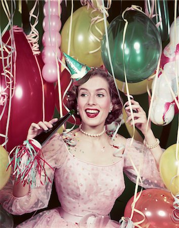 1950s HAPPY WOMAN IN PARTY DRESS PAPER HAT HOLDING NOISEMAKER HORN STREAMERS BALLOONS NEW YEARS EVE CELEBRATION Stock Photo - Rights-Managed, Code: 846-02794887