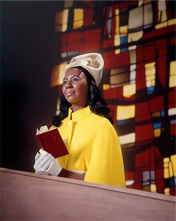 1970s AFRICAN AMERICAN WOMAN SITTING IN CHURCH PEW WEARING WHITE HAT GLOVES YELLOW COAT HOLD RED PRAYER BOOK STAINED GLASS BACKGROUND Stock Photo - Rights-Managed, Code: 846-02794892