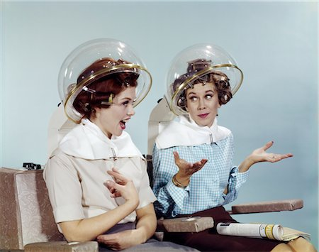 1960s TWO WOMEN SITTING UNDER BEAUTY SALON HAIR DRYER HOODS IN CURLERS TALKING GOSSIP Stock Photo - Rights-Managed, Code: 846-02795136