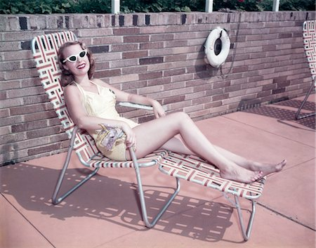 1950s SMILING WOMAN WEARING SUNGLASSES SUN BATHING IN DECK CHAIR CHAISE LOUNGE Stock Photo - Rights-Managed, Code: 846-02795158