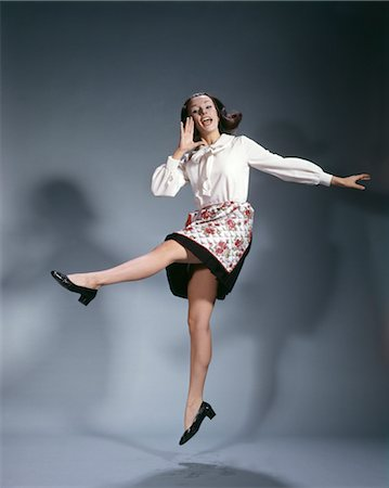 right - 1960s YOUNG WOMAN WEARING APRON JUMPING INTO THE AIR AND SHOUTING HAPPY SYMBOLIC KICKING JOY TRIUMPH Stock Photo - Rights-Managed, Code: 846-02795164