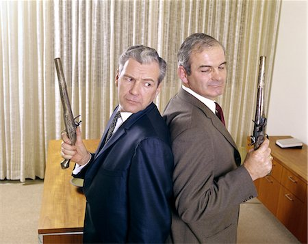 enemy - 1960s 2 MIDDLE AGED BUSINESS MEN STAND BACK TO BACK HOLDING GUNS PISTOLS DUEL DUELING ANGRY EXPRESSION ENEMY ENEMIES Stock Photo - Rights-Managed, Code: 846-02795169