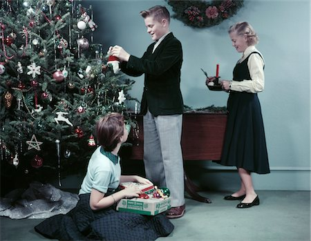 1950s TWO GIRLS AND ONE BOY DECORATING CHRISTMAS TREE WITH ORNAMENTS TEENS TEENAGERS HOLIDAY Stock Photo - Rights-Managed, Code: 846-02795247